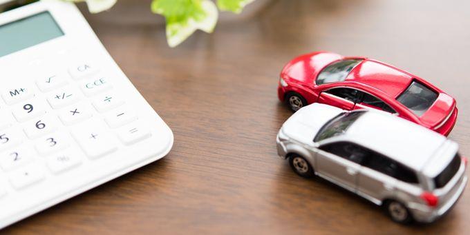 机の上に2台のミニカーと白い電卓