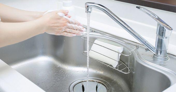 流しの水道で手を洗っている