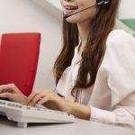 コールセンターでヘッドセットをつけて対応しながらキーボードを打つ女性の小さい画像