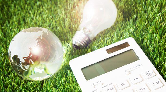 芝生の上の電球と水晶玉と電卓