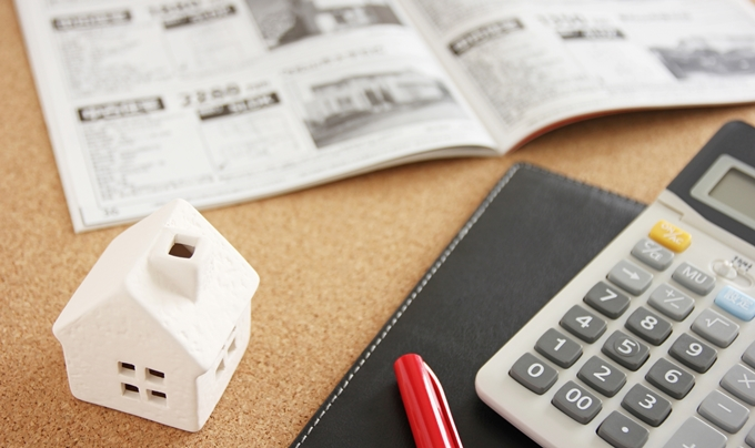 机の上に物件雑誌と電卓とペンと白い家の模型