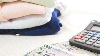 畳まれた洋服と電卓と千円札が床に置かれている小さい画像