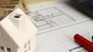 机の上にお金とペンと間取り図、白い家の模型の小さい画像