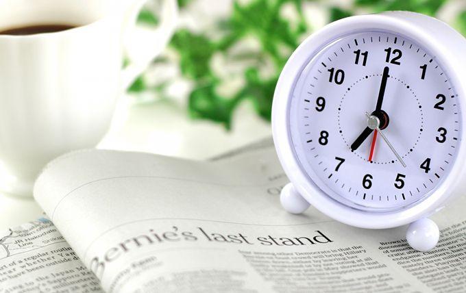 明るい部屋の机の上に、英語の本が開いた横に白い目覚まし時計がある