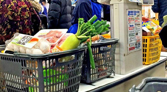 レジ台に大量の食品が入ったカゴが置かれている