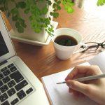 机の上にパソコンとコーヒーと眼鏡、そしてメモを取る手の小さい画像