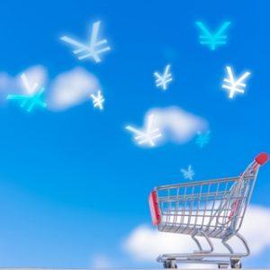 青空を背景にショッピングカートと、お金マークが飛んでいる小さい画像