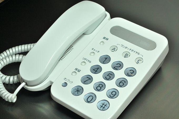 黒いデスクに置かれた白いプッシュフォン
