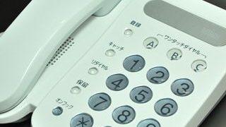 黒いデスクに置かれた白いプッシュフォンの小さい画像