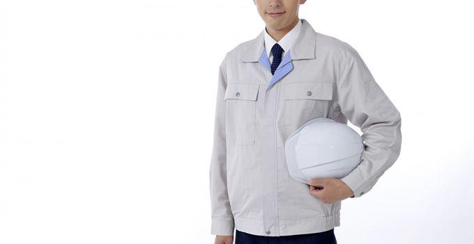 脇に安全ヘルメットを抱えたスーツに作業ジャンパーを羽織った男性が立っている