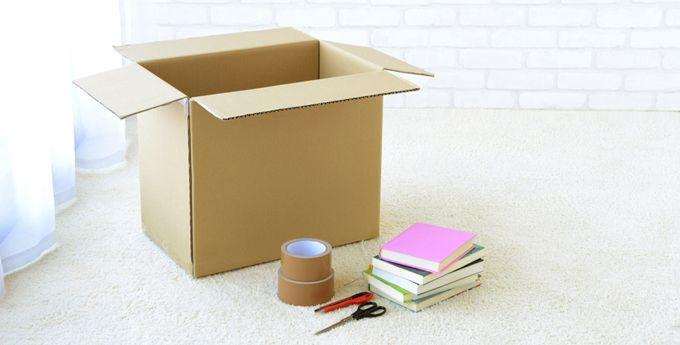 ダンボール、ガムテープ、ハサミ、本数冊が白い床に置かれている