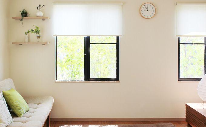 陽射しが差しこんでる白い壁のきれいな部屋いソファー