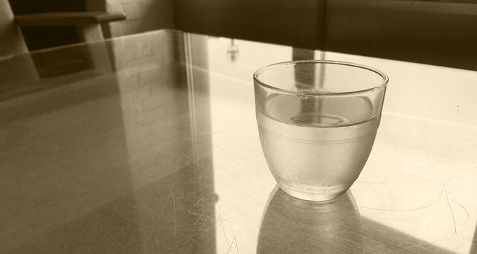 ガラステーブルに水が入ったコップが置かれている