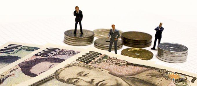 テーブルにお札と小銭が置かれ、その前にビジネスマンのフィギュアが3体