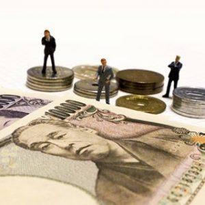 テーブルにお札と小銭が置かれ、その前にビジネスマンのフィギュアが3体の小さい画像
