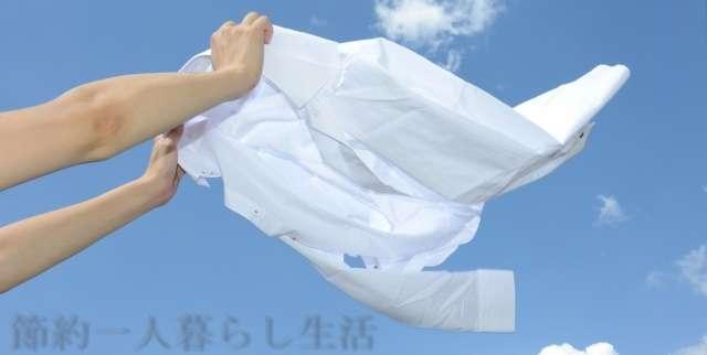 両手で青空に向かって白いワイシャツをバサッとなびかせている