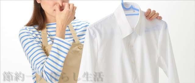 ボーダーを着てベージュ色のエプロンをしたロングヘアーの女性が白いシャツを持って鼻をつまんでいる
