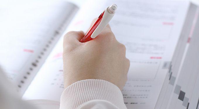 辞書に赤ペンを入れる女性の手