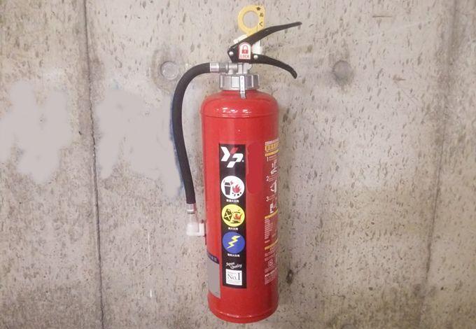 コンクリートの壁にかけられたABC消火器