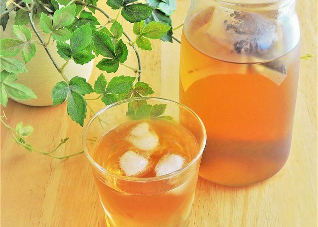 木のテーブルに置かれた麦茶が入ったビンとグラスと植物