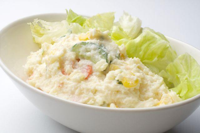 白い楕円形のボールに盛られた大量のポテトサラダとレタスの画像