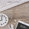 木の机の上にキーボード、時計、スマホ、クリップが乱雑に置かれている小さい画像