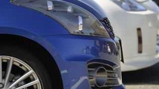 青い車と白い車が横に並んで頭部のみのアップ