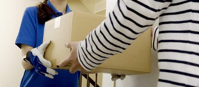 玄関先で荷物を受け渡しする拝承業者の女性と個人のお客さん