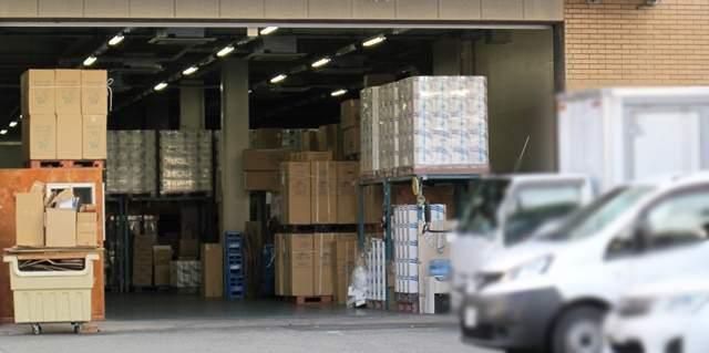 運送業者の搬入口に多数置かれた荷物と、脇に停まっている数台の車