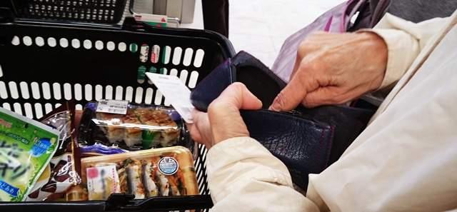 レジで商品が入った買い物かごを置き、財布から何かを出そうとしているご年配の女性の腕