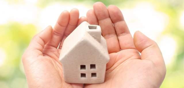 両手のひらに乗せられた紙粘土の白い家の模型