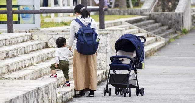 公園の入り口の階段の前で、母と幼子の後ろ姿とベビーカー