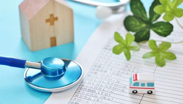 机の上に聴診器と血液検査の結果と植物と家の模型