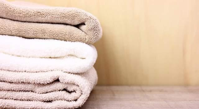 木製のキレイな棚に茶、白、ベージュのタオルが畳まれ積み重ねられている