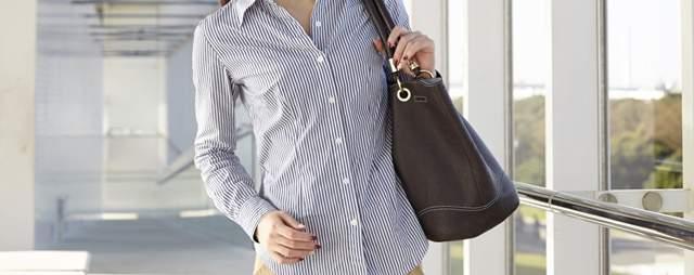 シャツ姿の女性がバッグを肩にかけて施設内を歩いている首から下の画像