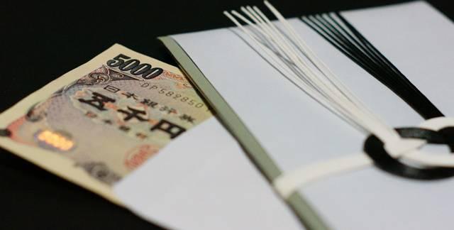 不祝儀袋とうち袋からはみ出した五千円札が斜めに重ねられている