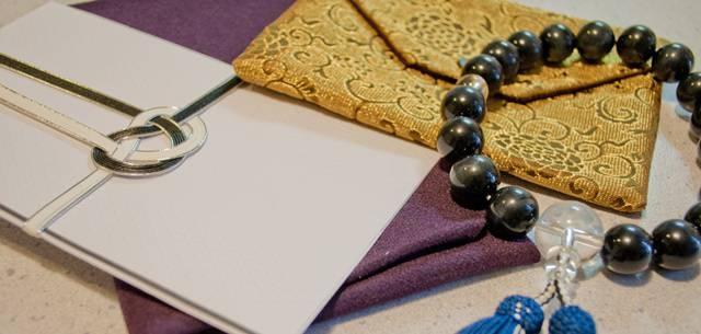 不祝儀袋、袱紗(ふくさ)、数珠が無造作に並べられている