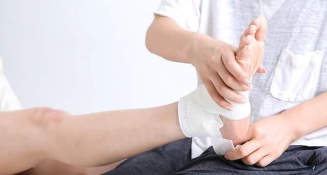 ケガをした人の足首に包帯を巻いている