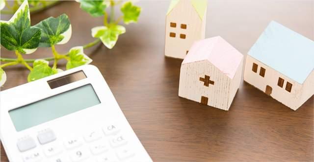テーブルに置かれた電卓と植物、かわいい小さな家のオブジェ