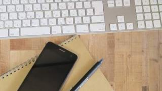 無造作に置かれたキーボード、ノート、ペン、スマホ