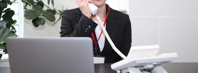 デスクの電話で話す女性。傍らにはパソコン
