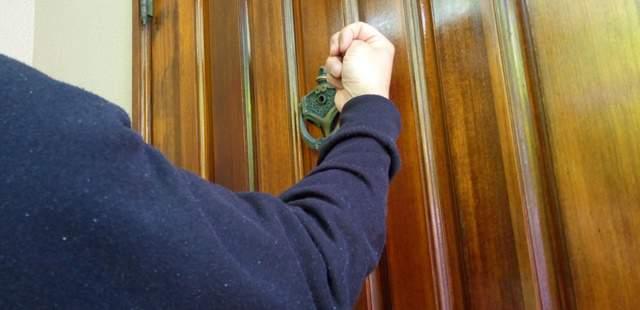 ドアをノックする男性の腕