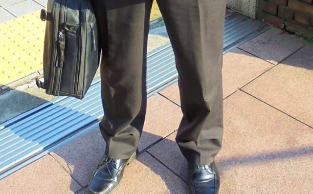 スーツを着て家の前に立つ男性の足元の画像