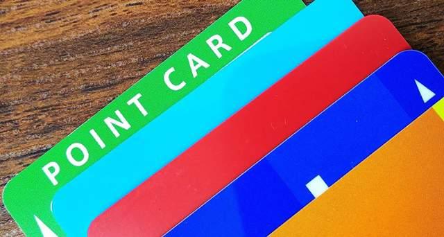 木の机に置かれた財布に入った複数のポイントカードが並んでいる