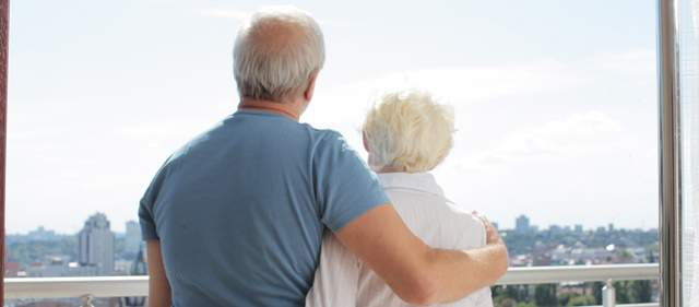 ベランダから肩を抱き合い外を眺める白人の老夫婦の後ろ姿