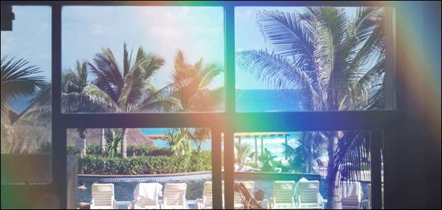 外国の別荘の窓からプールサイドとヤシの木の景色に虹がかかっている晴れた日の景色