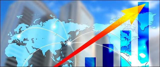 オフィスビル群を背景に、世界地図の上を赤い矢印が右上にグーンと上がるイラストが浮かんでいる