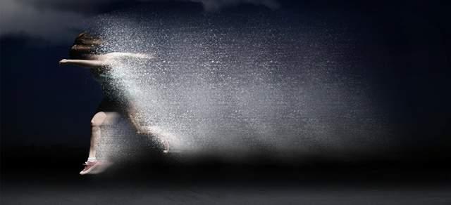 水しぶきを上げながら画面右から左へ向かって走る女性アスリートの残像
