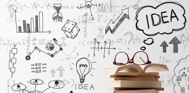 白い壁に様々なイラストがごちゃごちゃに描かれ、手前に本が積まれて一番上にメガネが逆さまに置かれている