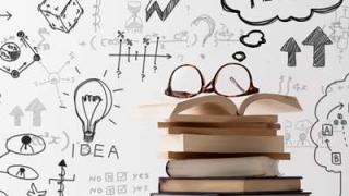 白い壁にIDEAという文字や電球にサイコロ、矢印など色んなイラストが描かれ、本が積まれている